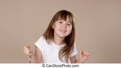Cute little girl in white tshirt dancing, smiling and having...