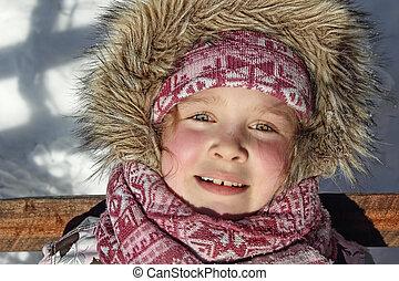 cute little girl in winter near wood