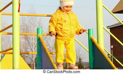 cute little girl in yellow on slide