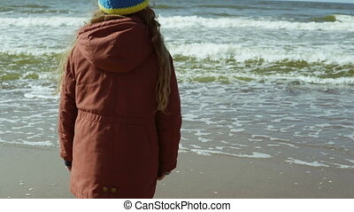 Cute little girl in yellow rubber boots standing on the shore of the sea and looking into distance, jumping. Back view.