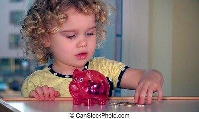 Cute little girl insert euro coins into piggybank. Static...