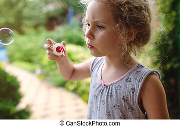 Cute little girl is blowing a soap bubbles , close up photo