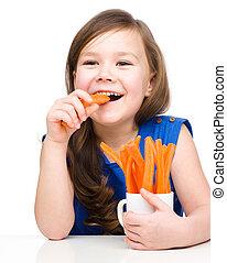 Cute little girl is eating carrot