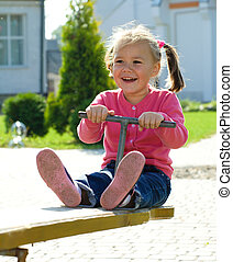 Cute little girl is swinging on see-saw - Happy little girl...