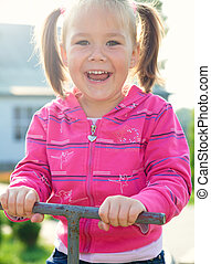 Cute little girl is swinging on see-saw