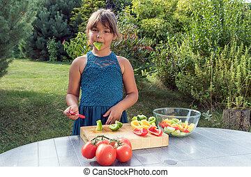 Cute little girl is tasting green pepper