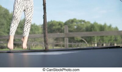 Cute little girl jumping on a trampoline in the summer outside