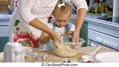 Cute little girl kneading baking ingredients in a mixing...