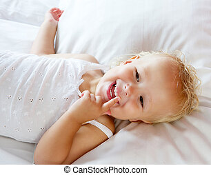 Cute little girl laughing in bed