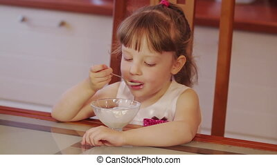 Cute little girl laughsing and eating ice cream in a bowl in the kitchen. Close up shot
