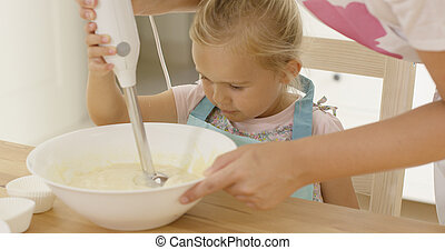 Cute little girl learning to bake from mother as she holds ...