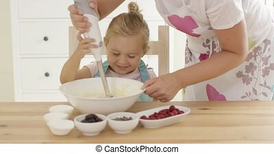 Cute little girl learning to bake from mother