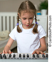 Cute little girl learning to play the piano.