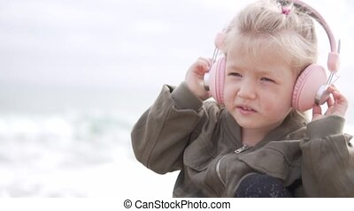 Cute little girl listening to music on headphones at the beach