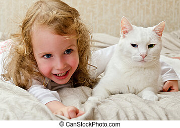 Cute little girl lying in bed with white cat