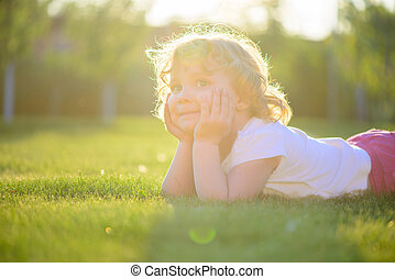 Cute little girl lying in green grass