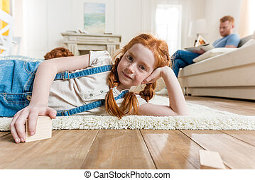 cute Little girl lying on floor with cubes at home