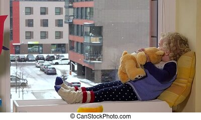 cute little girl lying on radiator by window with a teddy bear. winter snow fall