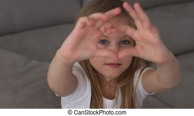 Cute little girl making a heart with her hands and smiling. Young beautiful girl smiling in love showing heart symbol and shape with hands. Romantic concept. Mothers Day