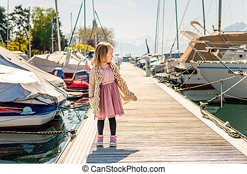 Cute little girl of 3-4 years old playing by the lake Geneva on a nice sunny day, standing on a pier between boats, wearing pink dress and golden cardigan, holding hands in pockets