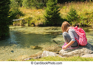 Cute little girl of 7-8 years old hiking in swiss Alps, resting by the river, wearing sport clothes, trainers and backpack, back view