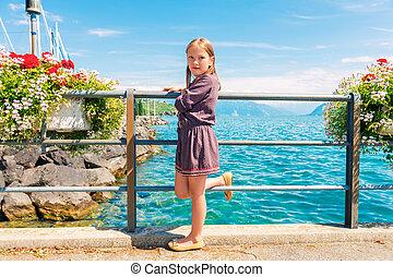 Cute little girl of 7-8 years old resting by the lake on a nice summer day