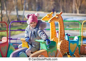 Cute little girl on carousel in the autumn park