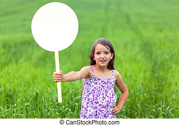 Cute little girl on neutral background holding sign used for your text