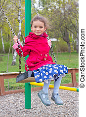 Cute little girl on playground in spring. Child in red jacket and blue dress with flowers on a swing on green spring park background