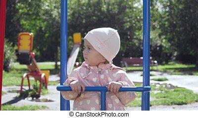 Cute little girl on swing in summer park. - Cute little...