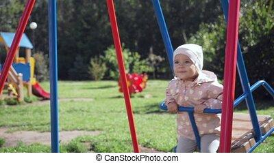 Cute little girl on swing in summer park.
