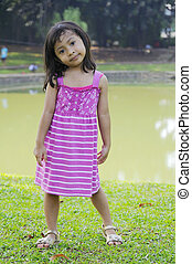 609483b745c7 Little girl in green dress barefoot standing on watermelon in the ...