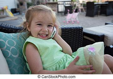 A cute little girl wearing a green dress using a cellular phone.
