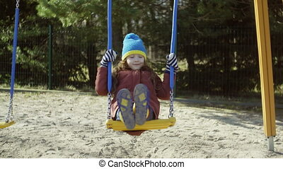Cute little girl on the swing. Beautiful child have fun outside on the playground. Female in bride clothes, rubber boots