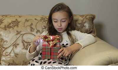 Cute little girl opens a gift box, surprise and joy
