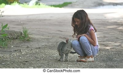 Cute little girl petting a giant black cat outdoors
