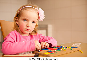 Cute little girl pin pointing blocks into wooden board playing with her toys