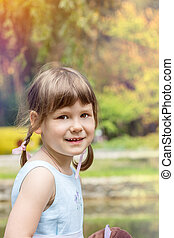 Cute little girl plaing in the city park on a summer sunny...