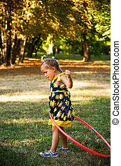 cute little girl play with hula hoop in park