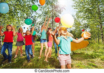 Cute little girl playing balloons with her friends