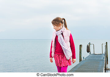 Cute little girl playing by the lake, walking on a pier, wearing pink waistcoat