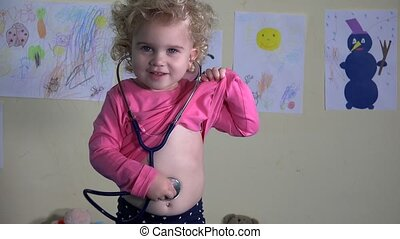 Cute little girl playing doctor at home with stethoscope....