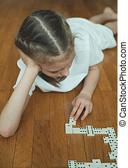 Cute little girl playing dominoes on the floor.