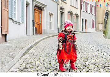 Cute little girl playing in a city, wearing princess costume