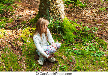 Cute little girl playing in a forest on a nice sunny day
