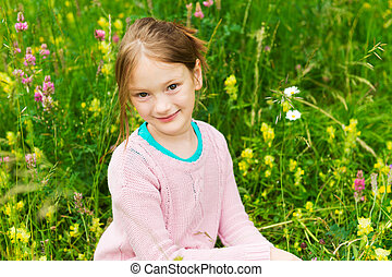 Cute little girl playing in a park, wearing pink pullover
