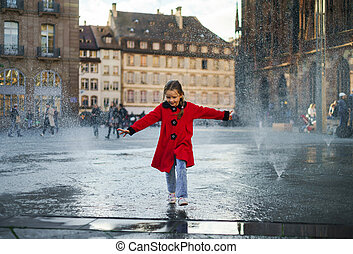 Cute little girl playing in water splash of street fountain