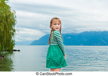 Cute little girl playing next to beautiful lake