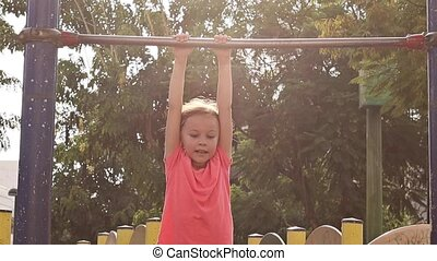 Cute little girl playing on playground and hanging on a...