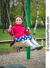 Cute little girl playing on playground in spring. Child in red clothes and blue dress with flowers on a swing on green spring park background